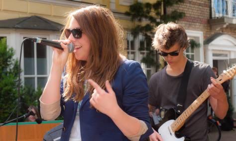 Eine Sängerin mit Gitarrist im Hintergrund