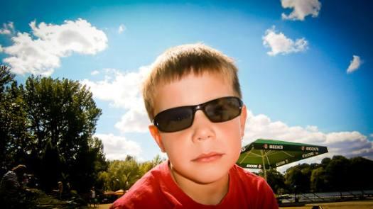 Junge mit Sonnebrille vor blauem Himmel