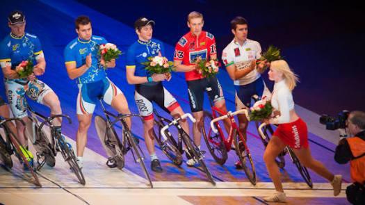 Cheerleaderin übebringt den Siegern des Radrennens einen Blumenstrauß