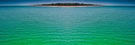 Grünes Meer mit Insel