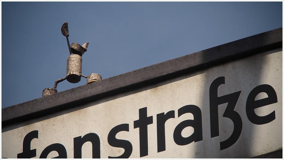 Korkmännchen auf einem Straßenschild in Berlin