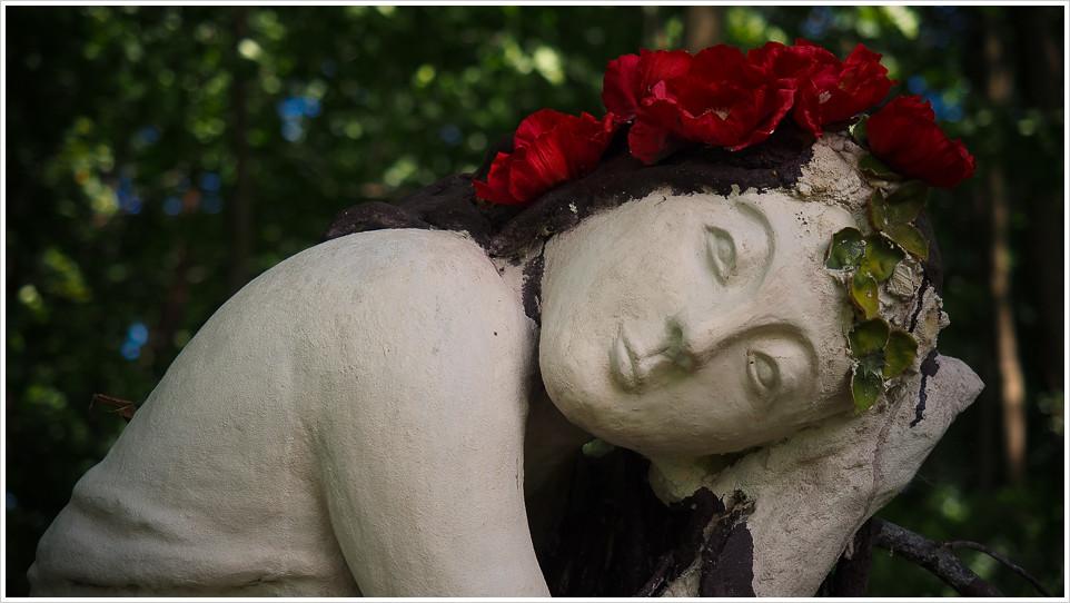 Weibliche Figur mit Rosen vor Bäumen