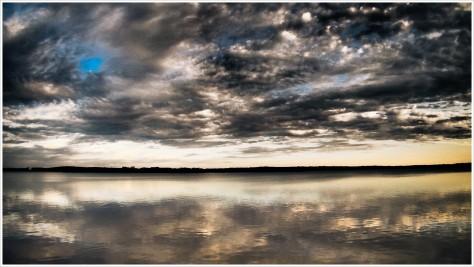 Dramatischer Wolkenhimmel spiegelt sich in See