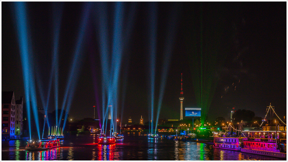 Nachtaufnahme von Schiffen mit Lichtstrahlen auf der Spree