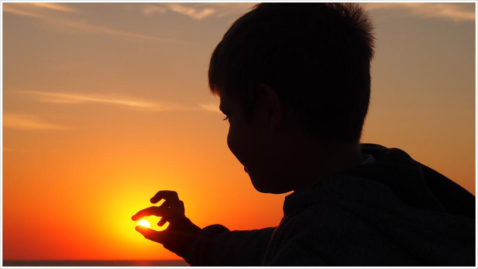 Kind im Schattenriss fängt die Abendsonne