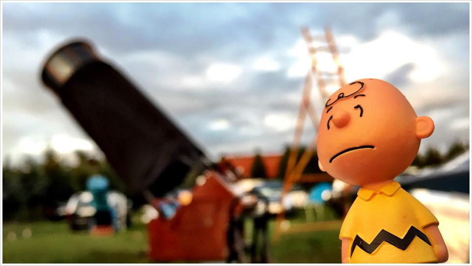 Charlie Brown vor einem Spiegelteleskop