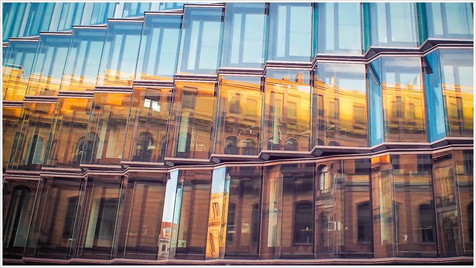 Ein Gebäude spiegelt sich in einer Glasfassade