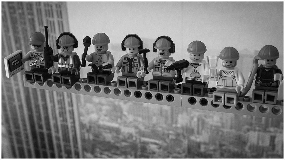 Legofiguren auf einem Träger, im Hintergrund die Kulisse von New York