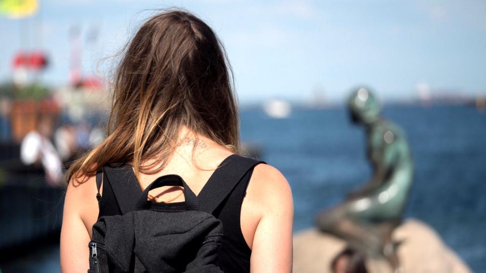 Frau vor der Meerjungfrau von Kopenhagen