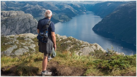 Mann schaut von oben auf Fjord