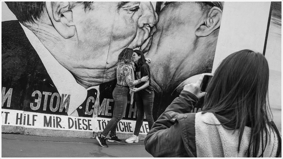 Zwei Mädchen küssen sich vor Bild der East-Side Gallery