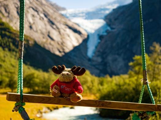 Elchfigur auf Schaukel vor Gletscher