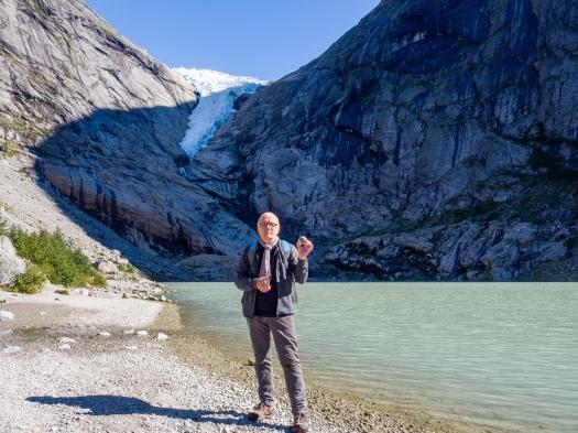 Mann steht an einem See mit Gletscher