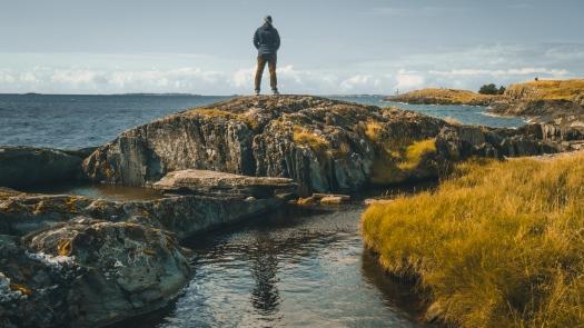 Mann steht auf Felsen und schaut aufs Meer