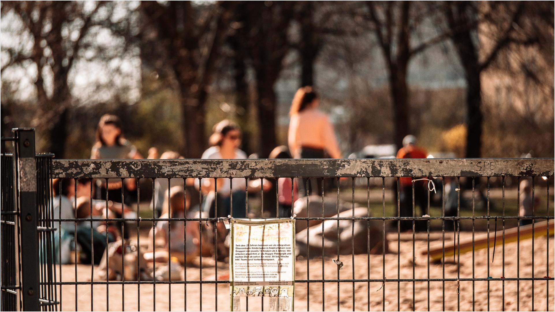Besucher eines Spielplatzes, unscharf hinter Zaun