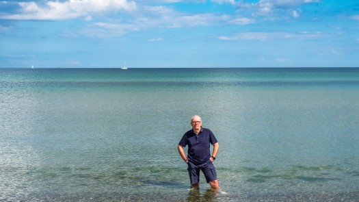 Eine Person steht bis zu den Knien im Meer