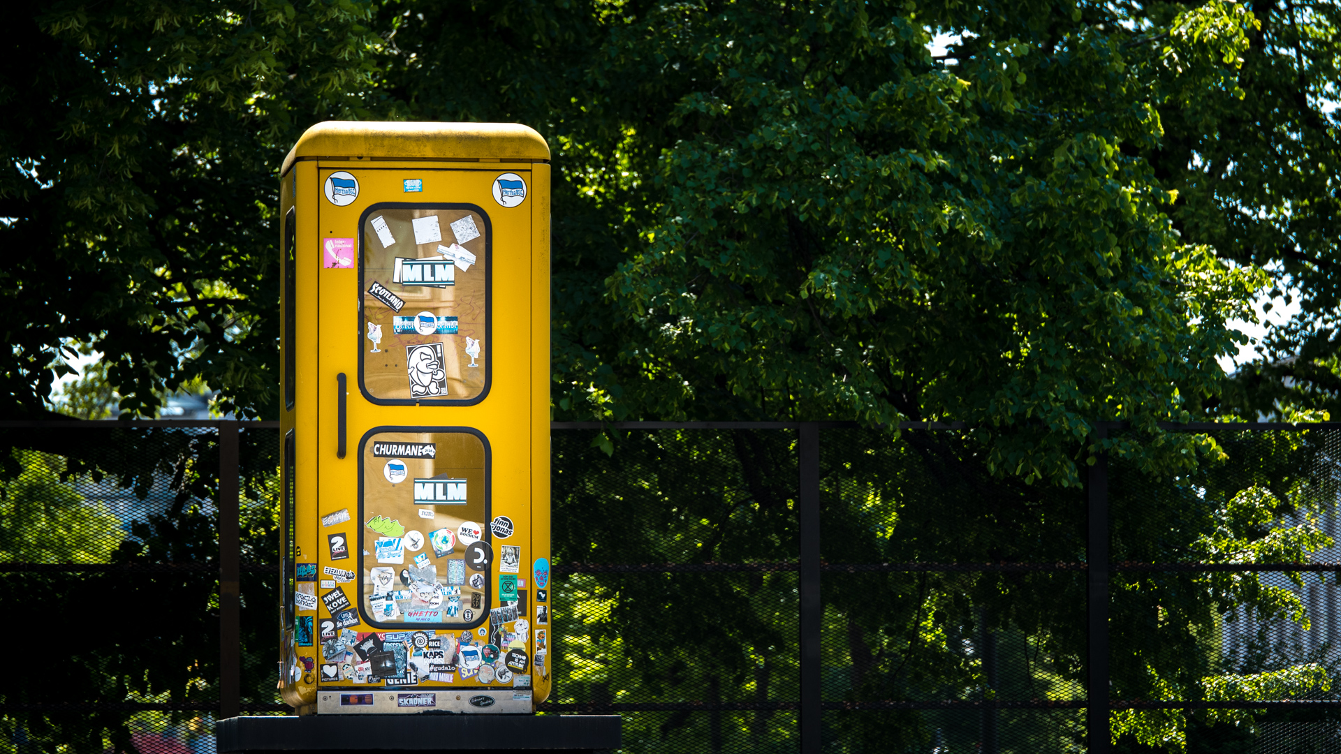 Gelbe Telefonzelle auf Sockel