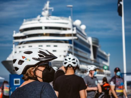 Frau mit Fahrradhelm vor AIDAsol im Hafen von Visby