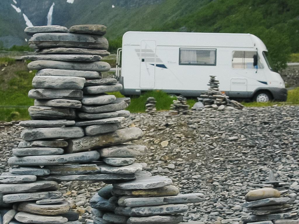 Steinpyramide in Norwegen, dahinter ein Wohnmobil